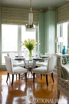 For a lighter look, fabric blinds replace swagged draperies at the dining room windows. Walls in a faux shagreen finish are Jill's favorite hue–Tiffany blue. Tufted chairs with nailhead trim introduce clean lines while remaining classic. A new chandelier was chosen to work with the apartment's new Art Moderne feel.