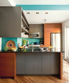 A Caribbean-colored backsplash livens up gray cabinets and a black stone countertop in this sleek cook space. | Jamaican Sea Ppg1236-6, PPG Pittsburgh Paints' The Voice of Color Program @voiceofcolor