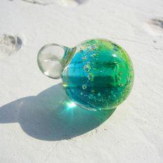 自宅工房にて、ガラスを融かして制作したアロマペンダントです。ターコイズブルーとシトラスグリーンのグラデーションに気泡をいれました。 太陽光に照らされると気泡に光が反射し、キラキラ感アップ!とても美しいです。 是非、自然光に照らしてみてください♪紐・・・ワックスコード(茶)約80㎝ (長さ調節できます) 玉サイズ・・・直径 約1.8㎜(多少誤差あり) ******************************* 使い方 玉の裏には穴が空いていて、そこにアロマオイルをちょこんと1滴垂らすだけです♪アロマオイル専用のスポイトもありますが、そのままでもOK♪ 1滴以上、数種類をミックスする場合などは、コットンなどに含ませてからご使用くださいませ〜(^。^)ガラスなので水で濯げます。 違った香りで何度もお楽しみ下さい(^^) 紐を替えればバックチャームやキーホルダーとしてもお使い出来ます。 ******************************** ハンドメイドのため、多少の個体差がありますこと ご了承ください m( )m◆ 送料には、梱包代が含まれています。『ブルーハ...
