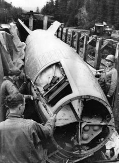 Soldiers of the US Army at Bomskirchen, Germany, inspect the control mechanism of a captured V-2 bomb. A trainload of V-2 bombs was captured. (Photo by Seigman/Getty Images)