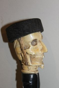 Walking cane with an ivory carved top of a jew, half man-half skull wearing a typical jewish hat. Raising Canes, Half Skull, Meerschaum Pipe, Cane Handles, Cane Stick, Chip Carving, Walking Sticks And Canes, Half Man, Umbrellas Parasols