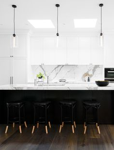 Black and white kitchen: white marble benchtops and splashback, white shaker cabinets with minimal black handles, timber floorboards, glass pendant lights with black cords, dining nook, bay windows, black dipped Thonet bentwood bar stools, skylights