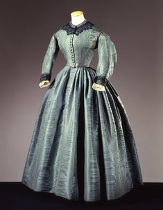 Early 1860s green moire taffeta dress trimmed with black and white lace and self-fabric ruching. Galleria del Costume di Palazzo Pitti, Italy.