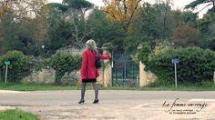 Auto stoppeuse. Femme faisant de l'auto stop sur une route de campagne, vue de profil avec un trench rouge et une jupe noire.