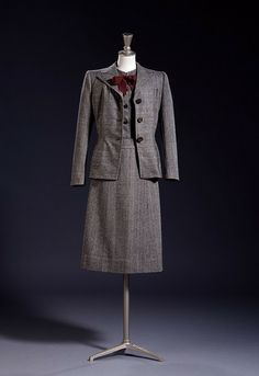 Original no. 16    Object:  Skirt suit    Place of origin:  London, England (made)    Date:  autumn 1942 (designed)    Artist/Maker:  Digby Morton, born 1906 - died 1983 (designer)   Incorporated Society of London Fashion Designers (producer (collection))   Utility (designed for)    Materials and Techniques:  Grey herringbone wool, fastened with metal buttons, trimmed with a grosgrain bow