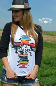 We're lovin' this new line from Crazy Train! Jump on board with our 'Serape War Paint' baseball tee. Buckin' bronc with serape cross in background. Love this awesome rodeo style. 3/4 length Black Ragl