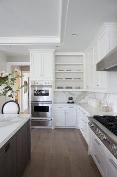 Two-tone kitchen with tray ceiling, floor to ceiling white cabinets, walnut kitchen island, marble slab countertops & backsplash and double ovens.