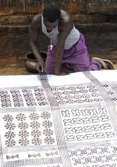 Anthony Boakye uses a comb to mark parallel lines on an adinkra cloth in Ntonso, Ghana.