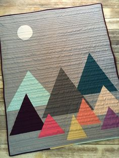 Love the mountains? Then youll love this beautiful crib quilt. Its the perfect compliment to any rustic, woodland, or outdoor themed nursery. Finished, it measures approx 40x50 fitting a standard crib mattress. Its a generous size for a newborn but offers years of snuggling and use as baby grows. This quilt is handmade using only the highest quality fabrics and batting. Backing is an ultra soft grey cuddle minky. It will be professionally longarm quilted for durability to last for years…
