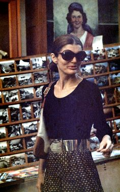 Jackie Kennedy Onassis in a midi skirt with a ruffled hem and the fabulous scoop necked, long sleeved shell with a belt and her famous over-sized sunglasses.