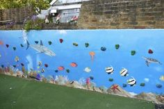 An underwater mural in London school playground. This was a blank wall with climbing stones attached to it. It has made a rather dull wall a fun feature in the school playground. It is heavily varnished so they can still climb on it too. - by Jess Arthur (great idea for back yard)