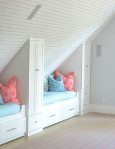 Attic bunk room features planked vaulted ceilings over built-in beds with storage dressed in pink and blu bedding flanked by built-in cabinets.