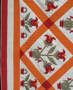 Close-up, Tulips quilt circa 1880.  Large tulips in a small pot with tiny red birds.  Hand quilting in a cable design in the border.  Seen at The Quilt Complex
