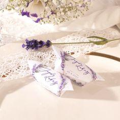 Dwie krówki w białych papierkach. Grafika przedstawia lawendowy wianek. Krówki leżą na beżowym talerzu. Wedding, Valentines Day Weddings, Weddings, Marriage, Chartreuse Wedding