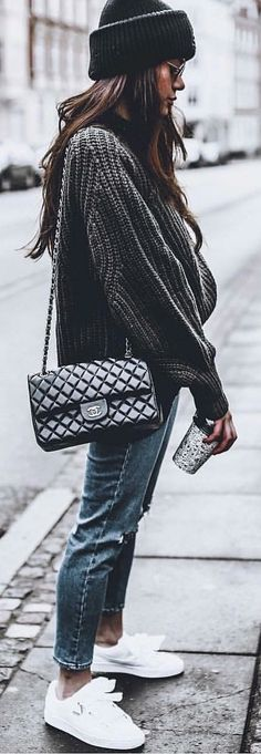 Grey sweater, quilted black Chanel crossbody bag, blue denim jeans and pair of white low-top lace-up shoes