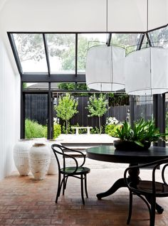 """Gallery: A magnificent monochrome home on Sydney's Lower North Shore:The atrium, added to the home during its previous renovation, overlooks a **garden** by [Peter Fudge Gardens](http://peterfudgegardens.com.au/?utm_campaign=supplier/ target=""""_blank""""). Thonet 'Le Corbusier' **armchairs**. Existing **dining table** was stained black. White **lampshades** and **urns** from [Les Interieurs](http://www.lesinterieurs.com.au/?utm_campaign=supplier/ target=""""_blank"""")."""