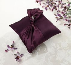 """Measuring 7.5"""" wide, this lovely ring pillow is covered in plum satin. The front is decorated with plum satin ribbon tied together with a diamond band ornament          #timelesstreasure"""