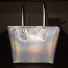 """COACH HOLOGRAM TOTE Hologram Crossgrain leather  Inside zip and multifunction pockets   Zip-top closure, fabric lining   Handles with 9"""" drop   Longer strap with 21 1/2"""" for shoulder or crossbody wear   11 3/4"""" (L) x 10 1/2"""" (H) x 5 1/2"""" (W)- straight from the store, I did notice a very slight surface scratch towards the bottom front (probably from being handled in store)- but so slight that I can't get it to show in a picture! NWT Coach Bags Totes"""
