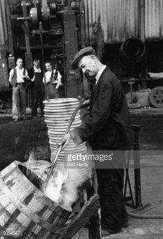 Guinness's burning off the loose wood splinters on the new barrels. by Gettysimages Barrels, Guinness, Dublin, Old Photos, Ireland, Irish, Wood, Places, Fictional Characters