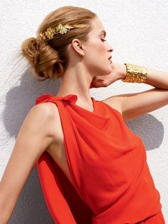 Grecian gold headband with an elaborate, looped chignon hairstyle | allure.com