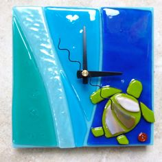 """Turquoise Blue Clock consists of Aqua, Bumpy Iridescent, Ocean Blue, and swirly Cobalt Blue wavy stripes with a Honu (Sea Turtle). measures about 6"""" square and sticks out of the wall about ½.""""Handmade on the Island of Hawaii by Shelly Batha"""
