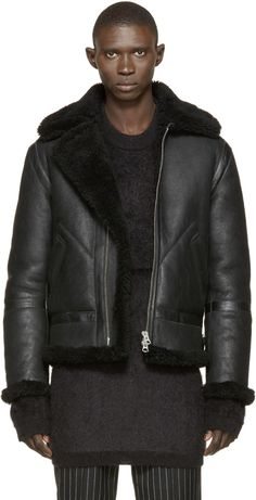 Long-sleeve lamb shearling jacket in black. Visible shorn wool at spread collar, cuffs and hem. Cinch strap with pin-buckle at collar base and at waist. Zipper closure at front. Buffed leather trims throughout. Eyelet vents at armscyes. Tonal stitching.