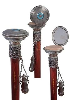 The perfect accessory for a lady adventuress! Cosmetic/Compact Powder Cane-Circa 1900-An enamel decorated powder box, probably silver, ornate pewter collar, hanging silver hallmarked perfume bottle, malacca shaft and a bimetal ferrule.