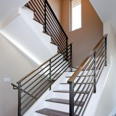metal stair railing with wood hand rail. attached to trim, not stairs