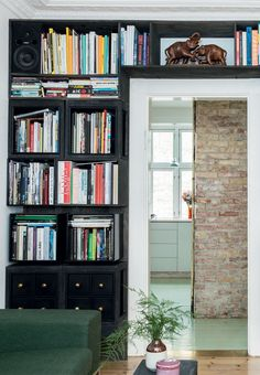 The door to the living room is surrounded by a large and beautiful shelving system.
