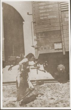 A partially clothed Jewish woman who is a passenger on the Iasi death train, walks beside the train during a stop on the journey. Romania, June  30th, 1941.