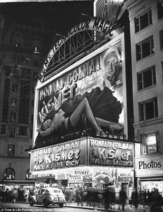 New Yorkers crowd Broadway below a large billboard depicting actress Marlene Dietrich over the Astor movie theater marquee in October, 1944