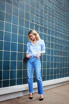 Adenorah in a button-down shirt tucked into high-waisted jeans, and black pumps
