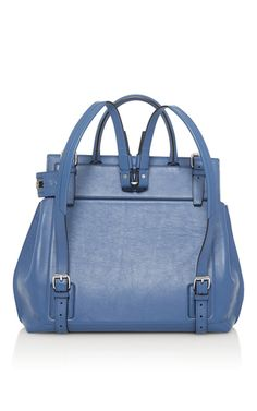 This backpack by **Elena Ghisellini** is rendered in blue sensua leather and features a structured body with an easy reach front zipper pocket with a braided pull and top handle.