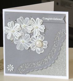 Silver and white wedding card. Stampin Up flowers stamped and heat embossed in white. Edged with Spellbinders borderabilities - Curved Borders 2.