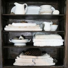 Ironstone, grain sacks and old linens in an antique cupboard  at home on SweetCreek