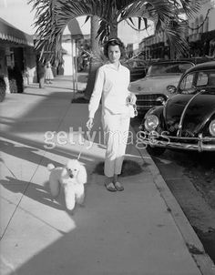American socialite and art collector Jayne Wrightsman walks her pet poodle on Worth Avenue, Palm Beach, Florida, 1960s. (Photo by Bert Morgan/Getty Images).