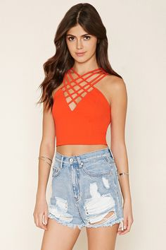 This sleeveless stretch knit top features a prominent lattice cutout V-neckline and an exposed back zipper.