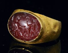 Charmante bague en or fin (20 – 22 K). L'anneau large est constitué d'une épaisse feuille d'or convexe. Il est surmonté d'un chaton en bâte sertissant une intaille ovale en cornaline d'une très jolie teinte rougeâtre. Elle représente une scène de l'Olympe où Jupiter trônant, l'aigle à ses pieds, reçoit une couronne de laurier de la déesse Victoire ailée. Une inscription en caractères grecs est gravée sur la champ. La pierre est très finement gravée.Très bon état, avec un léger éclat en ...