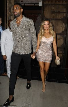 Night out: Khloe showed off her workout-honed body in a low-cut shimmery mini dress with a lacey hem paired with silver strappy sandals