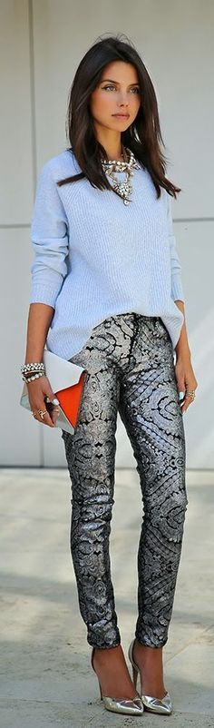 Chestlength dark hair, sky blue sweater, formfitting silver/black patterned pants, silver pumps