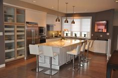 Modern kitchen featuring hardwood floors and a regular ceiling lighted by recessed and pendant lights. The center island offers a breakfast bar and has white modern seats. Kitchen Layout, New Kitchen, Kitchen Dining, Kitchen Decor, Kitchen Ideas, Dining Room, Small Kitchen Pictures, Kitchen Images, Kitchen Island With Seating