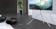 햇살이 드는 거실에 TV스탠드 위에 올려진 TV가 보입니다. TV화면 안에는 바다 풍경이 보입니다.