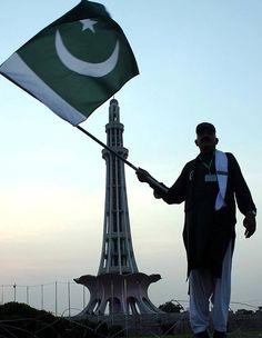 A man waves national flag near Minar-e-Pakistan.
