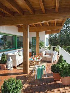 un mobilier en rotin clair et un revêtement de sol en bois sur la terrasse