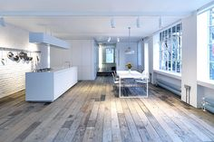 The huge open-plan main room has a simple white Corian-type kitchen island and huge warehouse windows.  http://www.homesandproperty.co.uk/your_home_and_garden/my_home/perlmanhome.html