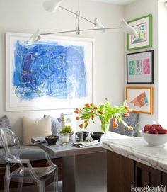 """Children's art projects are given the artist treatment with frames in this Park Avenue apartment's kitchen. """"I thought the apartment should reflect the fact that it's for a young, modern family with three children and a broad, cosmopolitan view of the world,"""" says designer Eric Cohler. A David Weeks lighting fixture animates the corner."""