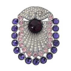 "Beautiful large piece by Eisenberg of oval shape, the stones worked like spread peacock feathers and consisting of clear and pink crystals bordered by blue cabochons and with a deep purple cabochon at center, all set into a silver metal mount. Marked ""Eisenberg/Originals"" on back.1950s"