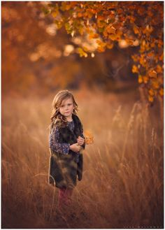 Warm, autumn portrait of a cute little girl with freckles taken outside underneath a tree with fall colors near Las Vegas