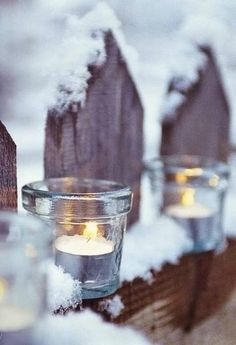 tea lights outside on the fence in the snow