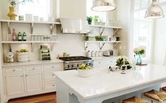 Bright, light kitchen with open shelves: Love the idea of combining a white painted kitchen with bright popping details here and there, such as vases, jars and flowers